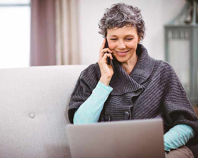 Mature woman with laptop talking on mobile phone at home