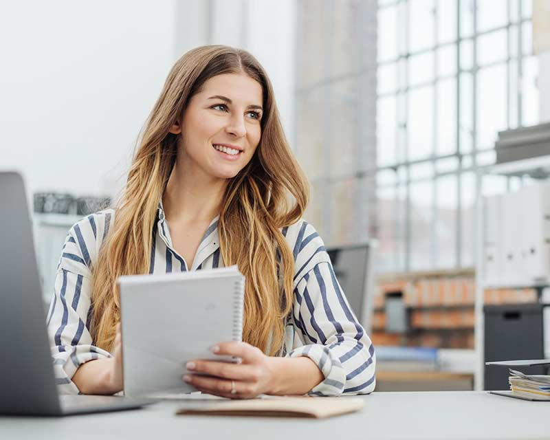 Young smiling woman holding notepad in office