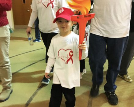 Child at heart run and walk holding torch sign