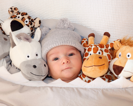photo of a baby next to stuffed animals
